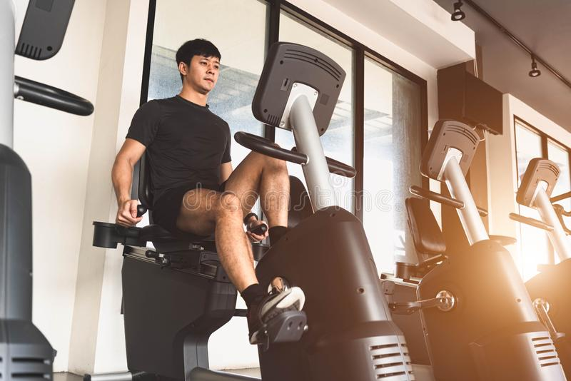Asian young sport man riding stationary bicycle in fitness gym. Man working out on spinning bikes in gym. People lifestyles and royalty free stock images