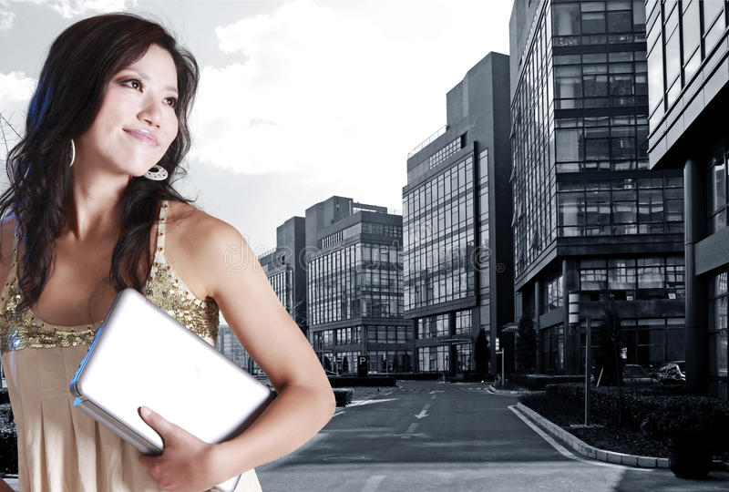 Asian young woman. Holding a laptop in modern office district stock image