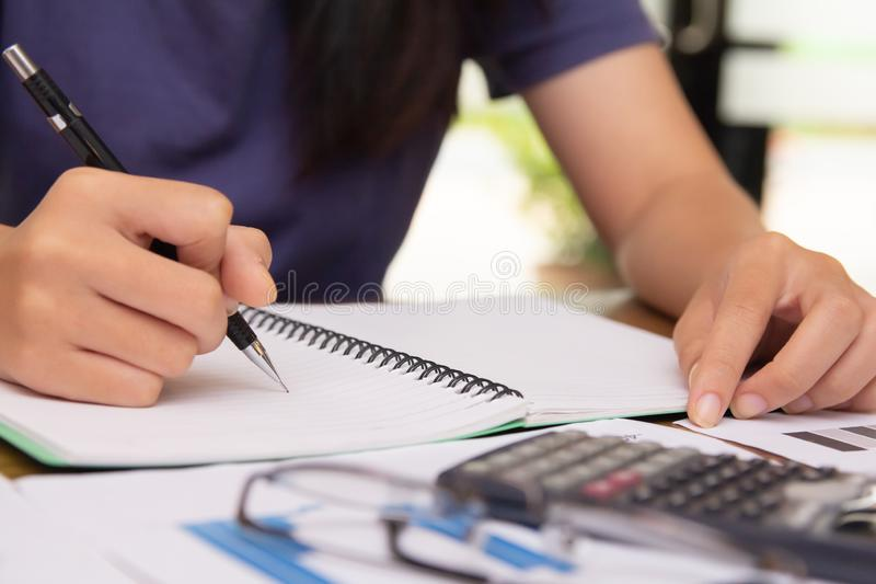 Asian young woman in blue shirt holding pen working ,Calculate tax lead to liquidation royalty free stock image