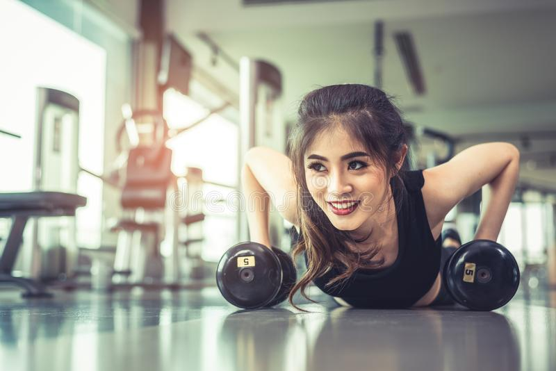 Asian young woman doing push ups with dumbbell on floor in fitness gym and equipment background. Workout and Sport Exercise royalty free stock photos