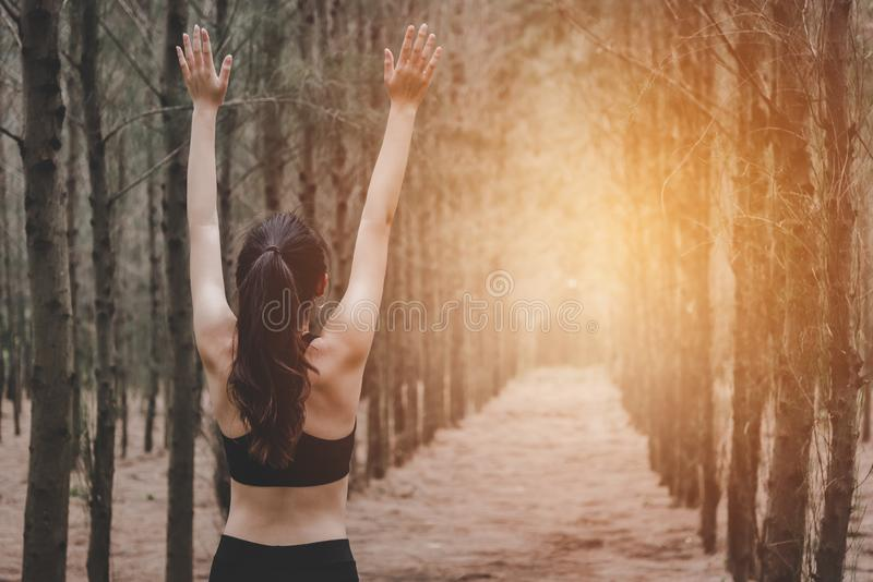 Asian young woman doing yoga and spreading arms in forest. Back view. Nature and Healthy Sport concept. Inhale fresh air in the stock images