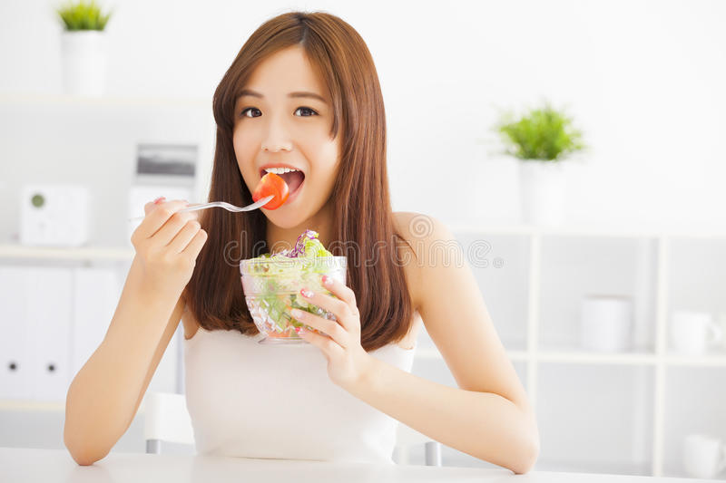 Asian young woman eating healthy food. Beautiful asian young woman eating healthy food royalty free stock photography