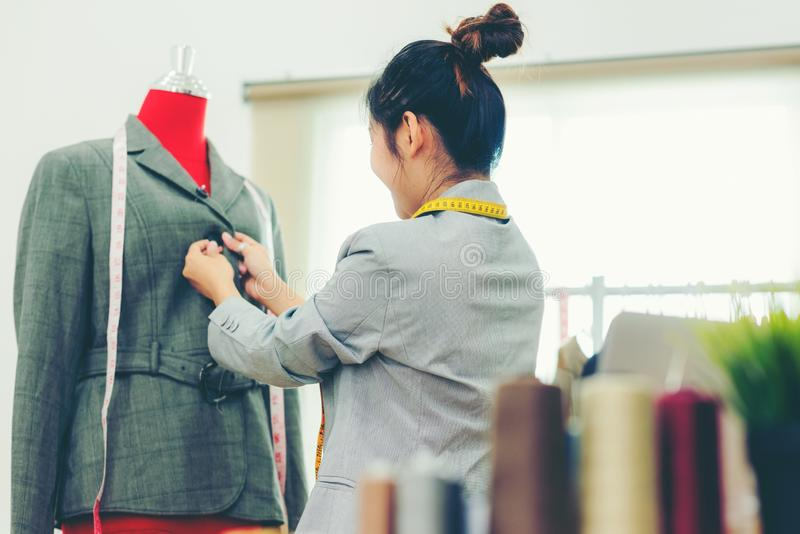 Asian young women fashion designer  working on her designer in the showroom,  Lifestyle Stylish tailor taking measurements on mann royalty free stock photography