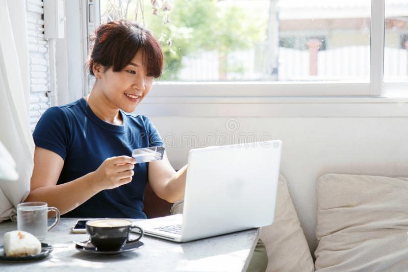 Asian young woman holding credit card and using laptop computer. royalty free stock images