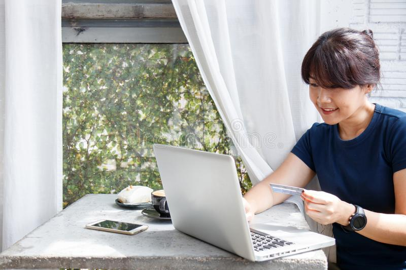 Asian young woman holding credit card and using laptop computer while sitting in cafe. Online shopping concept. Copy space. royalty free stock photos