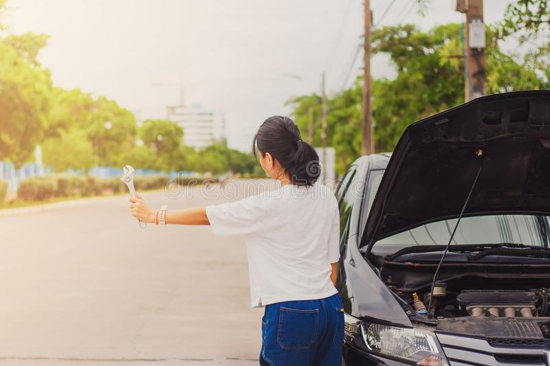 Asian young woman holding a wrench and hitch-hiking for help while the car broken down stock images