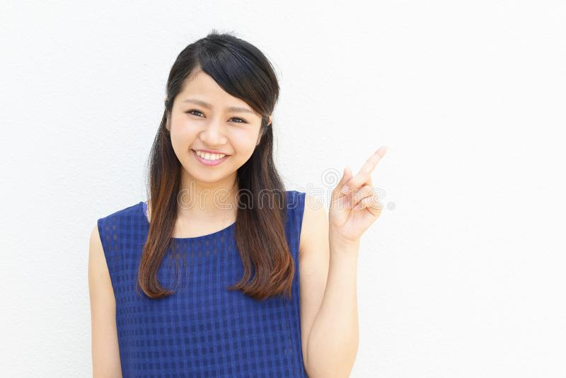 Beautiful young woman smiling. Asian young woman pointing with her finger stock image
