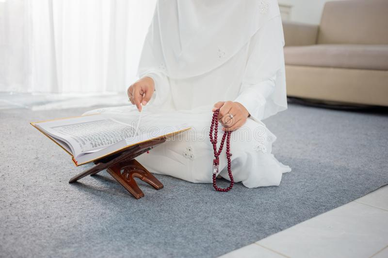 Asian young woman praying with Al-Qur`an and prayer beads. In white traditional clothes stock image