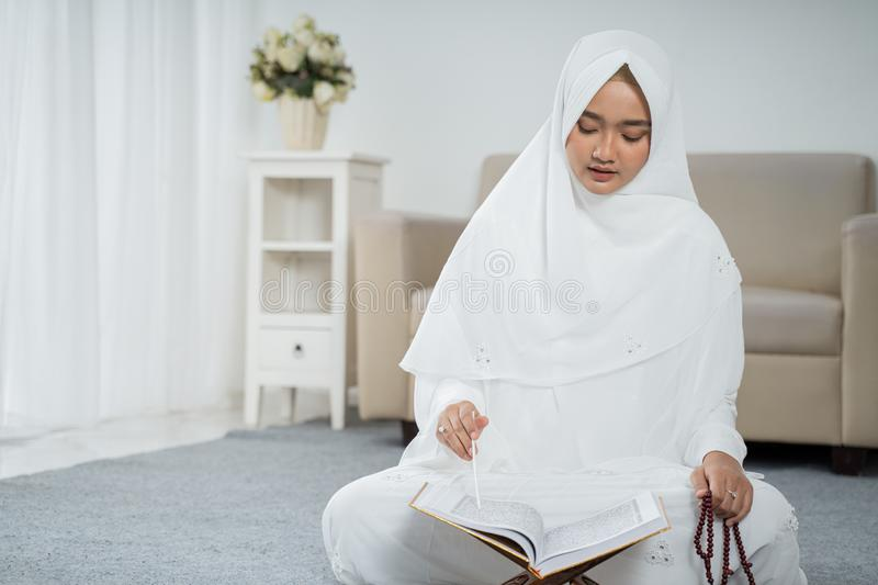 Asian young woman praying with Al-Qur`an and prayer beads. In white traditional clothes stock photo