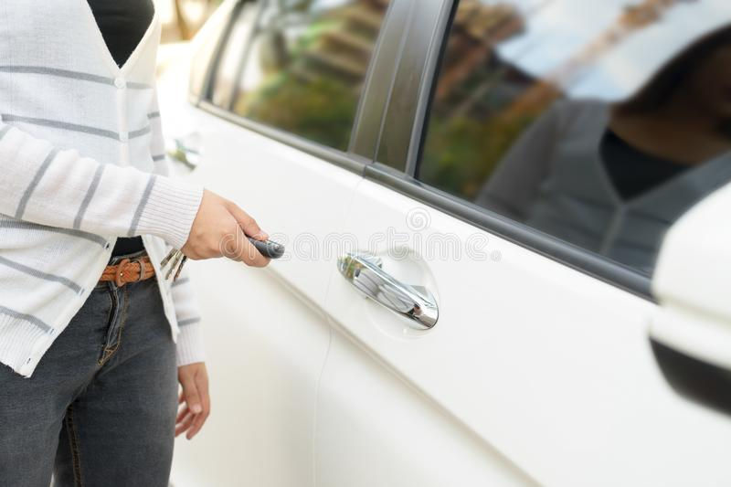 Asian young woman presses unlock button on remote control car key for opening car door. royalty free stock image