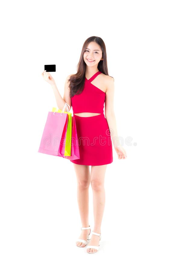 Asian young woman with red dress holding a credit card and bag paper colorful isolated. On white background royalty free stock photos