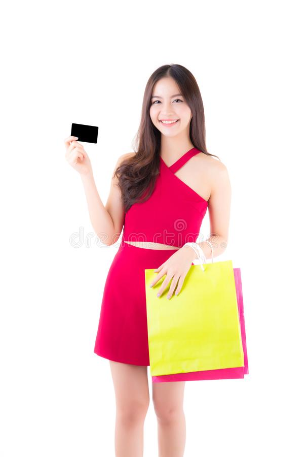 Asian young woman with red dress holding a credit card and bag paper colorful isolated. On white background royalty free stock image