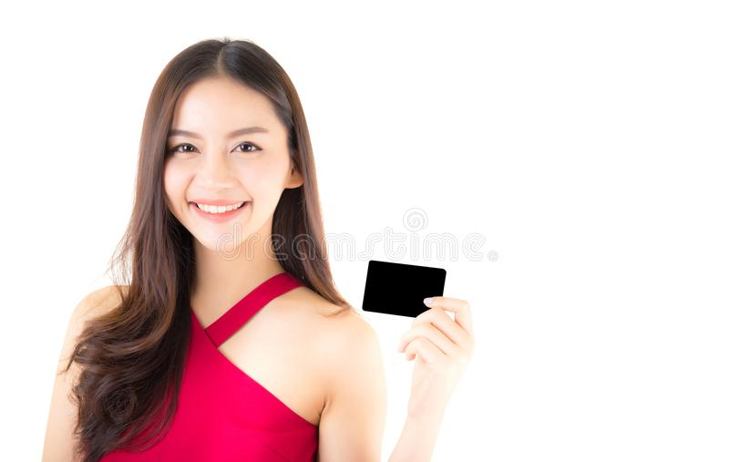 Asian young woman with red dress holding a credit card thinking to spend money lots isolated. On white background stock photography