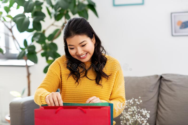 Asian young woman with shopping bag at home. People and leisure concept - happy smiling asian young woman in yellow sweater with shopping bag sitting on sofa at royalty free stock photography