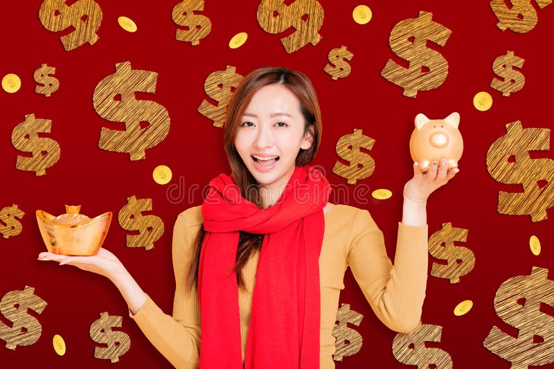 Asian young woman showing the gold piggy bank celebrating for chinese new year.  royalty free stock photo