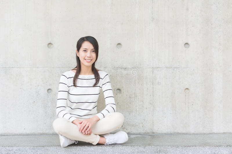 Asian young woman sit. With copyspace on wall royalty free stock photo