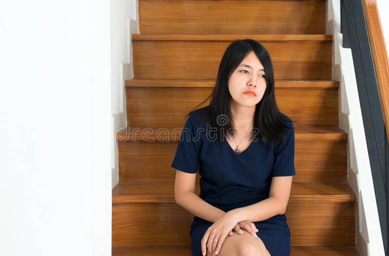 Asian young woman sitting on stair with depression of lonely have a headache,Be absent-minded,Mental disorder health care concept stock photos