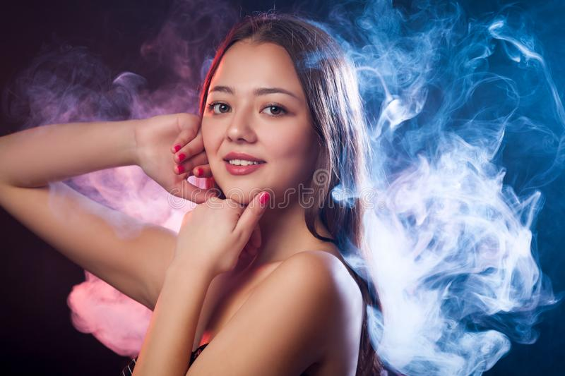 Asian dark-haired woman. Asian young woman smile and posing against a background of red and blue smoke from a vape on a black isolated background stock photography