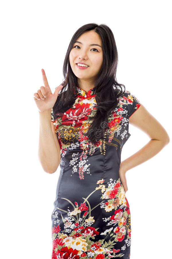 Asian young woman smiling and pointing upwards. Young attractive Asian woman in her 20's shot in studio isolated on a white background stock photo