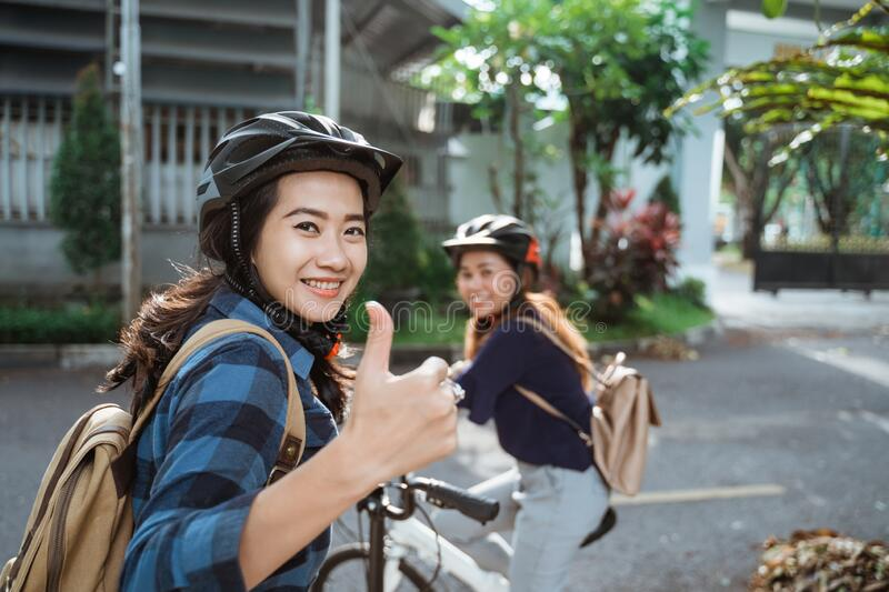 Asian young woman with thumbs up wearing helmet and bags ready go to campus royalty free stock image