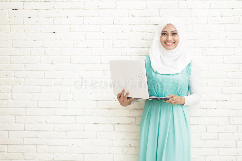 asian young woman wearing hijab holding a laptop stock images