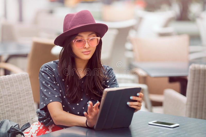 Asian young woman working with mobile phone and tablet computer in cofe shop. royalty free stock images