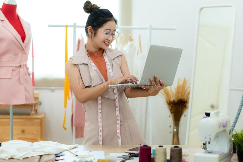 Asian young women fashion designer  using laptop working and design tailor and cloth in the showroom,  Lifestyle Stylish tailor ta stock photos