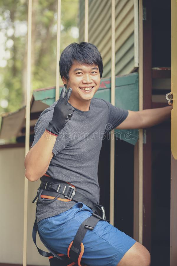 asian younger man wearing safety harness suit preparing to hiking artificial cliff in adventure base royalty free stock images