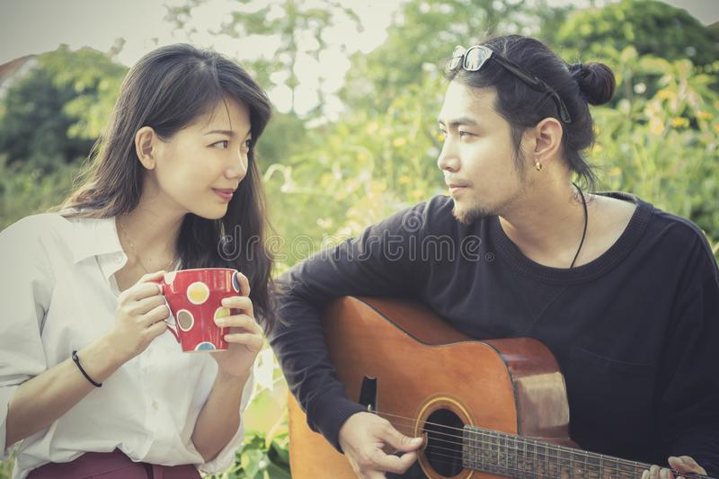 asian younger man and woman playing guitar with happiness emotion stock photos