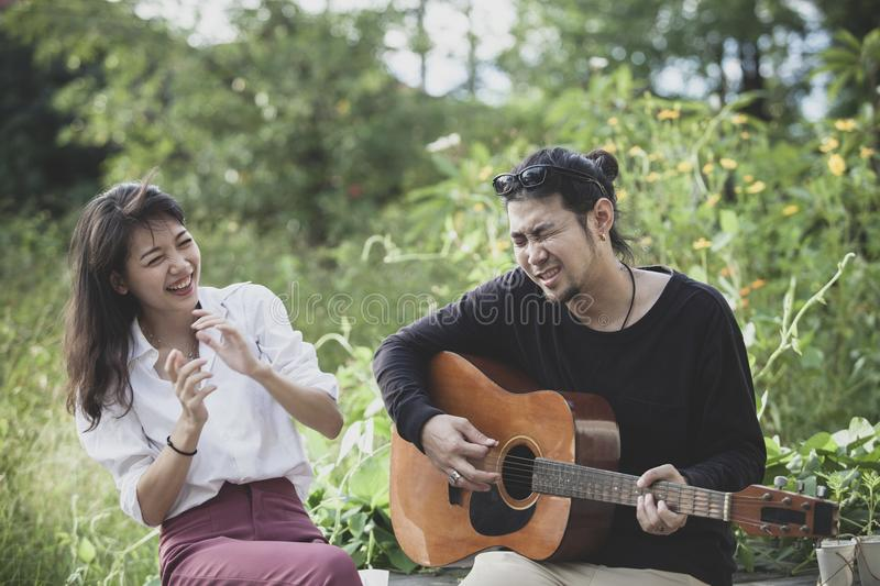 asian younger man and woman playing guitar with happiness emotion royalty free stock image