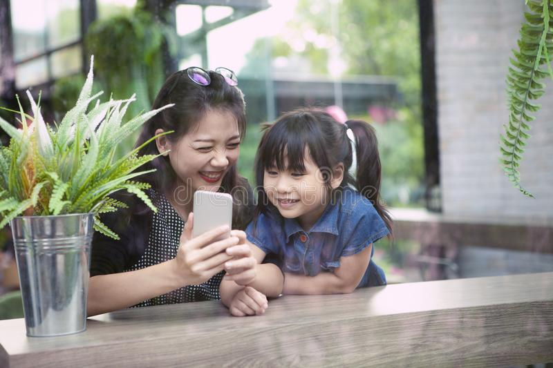 Asian younger woman and children looking to smart phone screen at home living room royalty free stock image