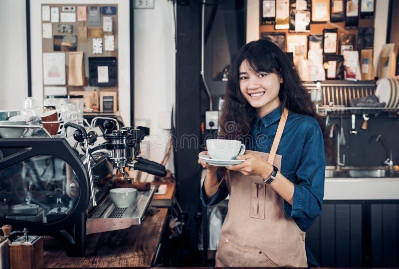 Asiat Barista diente Kaffee oben mit L?cheln am Caf?holdingbecher mit Hand zwei mit l?chelndem Gesicht am Caf?barhintergrund stockbild
