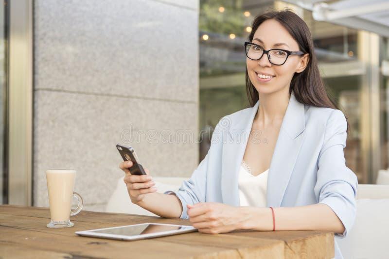 Asiat-Caucasian kvinna som sitter på kafét i smart tillfällig dräkt arkivfoto