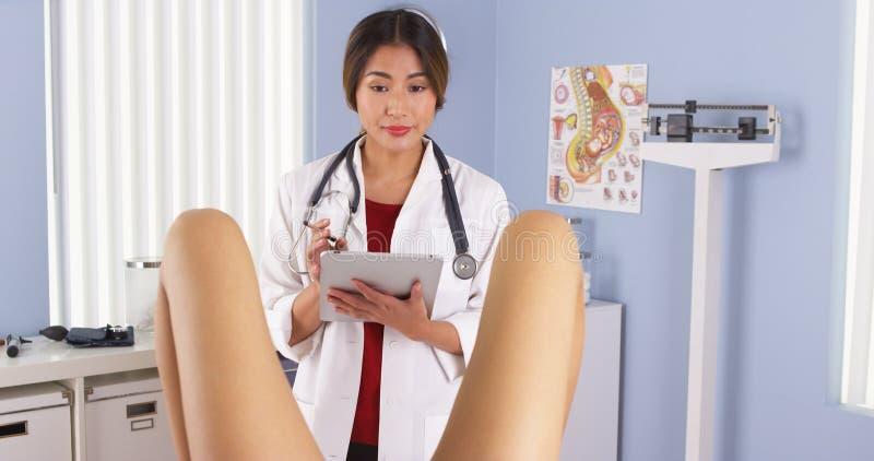 Asiat OBGYN som undersöker den gravida patienten arkivfoto
