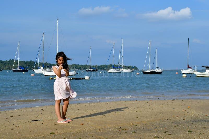 Asiat som är tonårig med kameran på den sandiga stranden royaltyfria foton