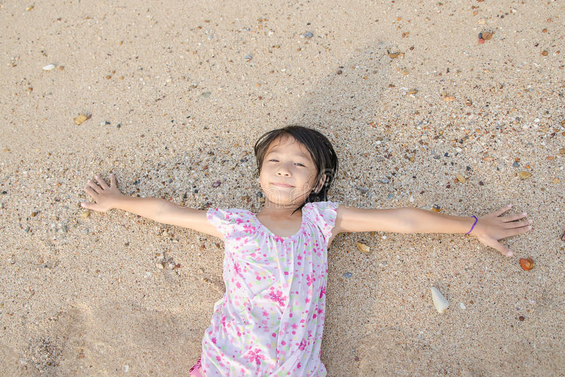 Asiat som ler den gulliga lilla flickan som ligger på strandsanden Thailändsk chi royaltyfri foto