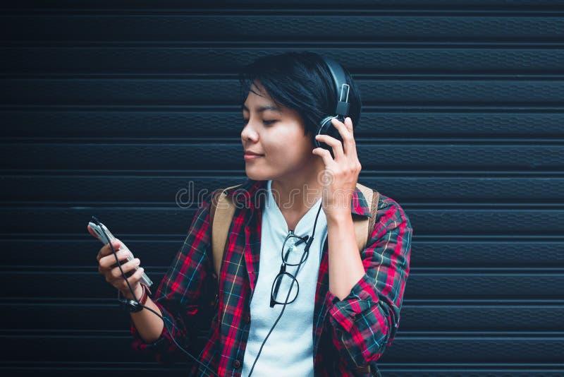 asiat Tonåret lyssnar till musik på nära område med tappningsignal royaltyfria bilder