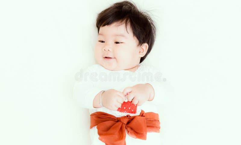 Asiatet behandla som ett barn den gulliga flickan som ler på sängen för bakgrund fotografering för bildbyråer