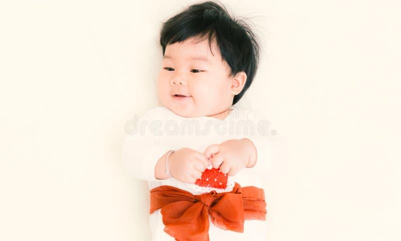 Asiatet behandla som ett barn den gulliga flickan som ler på sängen för bakgrund Inte gör de ser smaskiga royaltyfri bild