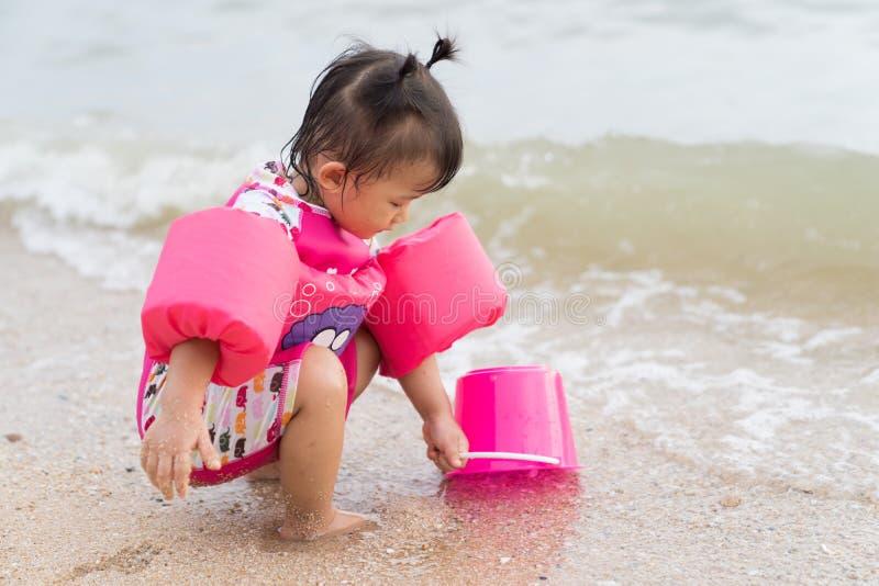 Asiatet behandla som ett barn flickan som är skämtsam på strandbakgrunden fotografering för bildbyråer