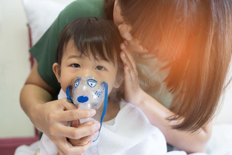 Asiatet behandla som ett barn flickan andning sombehandling med modern tar omsorg, på ro royaltyfria foton