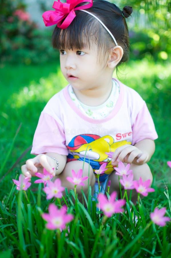 Asiatet behandla som ett barn flickan med blomman royaltyfria bilder