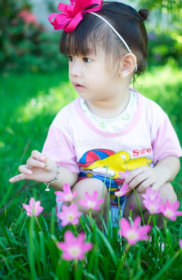 Asiatet behandla som ett barn flickan med blomman arkivbild
