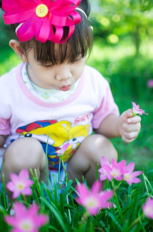 Asiatet behandla som ett barn flickan med blomman royaltyfria foton