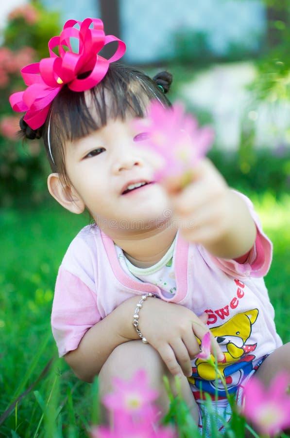 Asiatet behandla som ett barn flickan med blomman arkivbilder