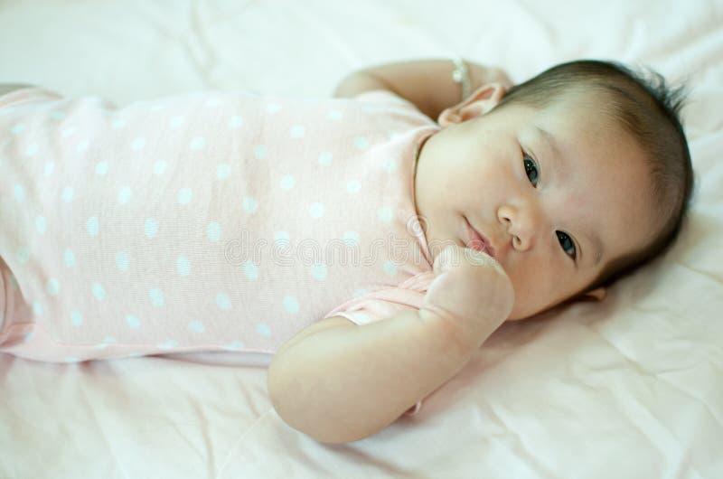 Asiatet behandla som ett barn flickan som lägger på säng royaltyfri fotografi