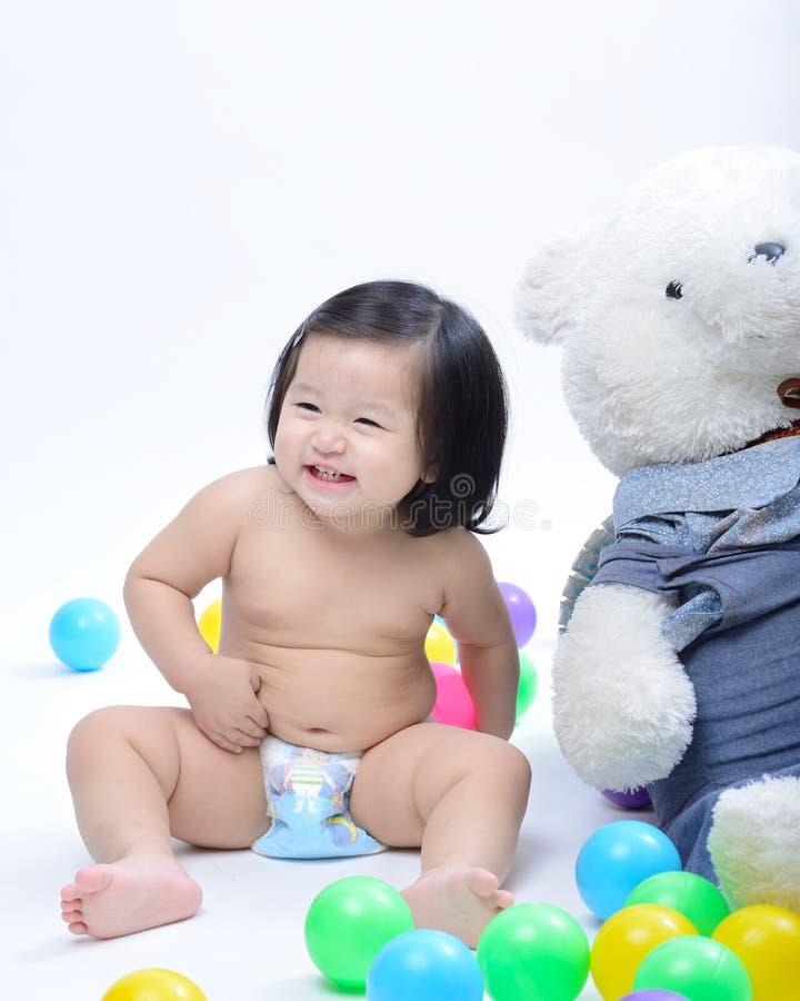 Asiatet behandla som ett barn flickan som ler, och att sitta spelar med färgrik bal royaltyfri bild