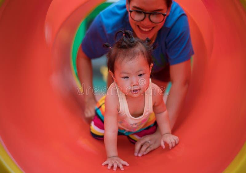 Asiatet behandla som ett barn flickan som spelar med mamman p? lekplats royaltyfria bilder