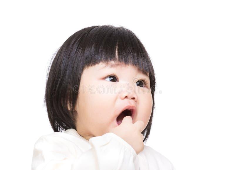 Asiatet behandla som ett barn flickan suger fingret in i mun royaltyfria bilder