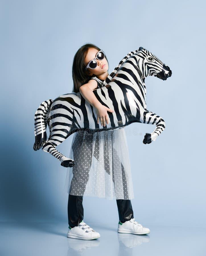 Asiatet behandla som ett barn flickaungen i modekläder, och solglasögon poserar med den metalliska ballongen för sebran som hon h arkivbild